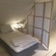 Der Schlafbereich im Loft ist durch Paravents vom Wohnbereich abgetrennt