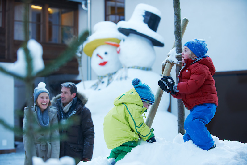Die Kids bauen auf dem autofreien Platz Schneemänner während die Eltern bummeln und shoppen